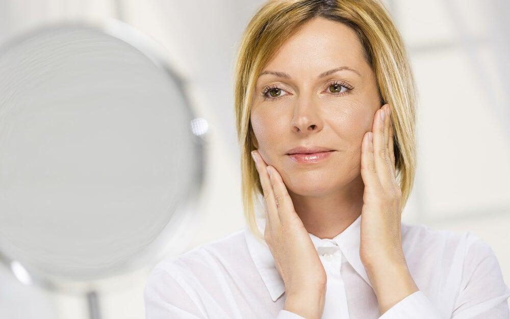 Mujer mirándose al espejo y estirándose la cara.