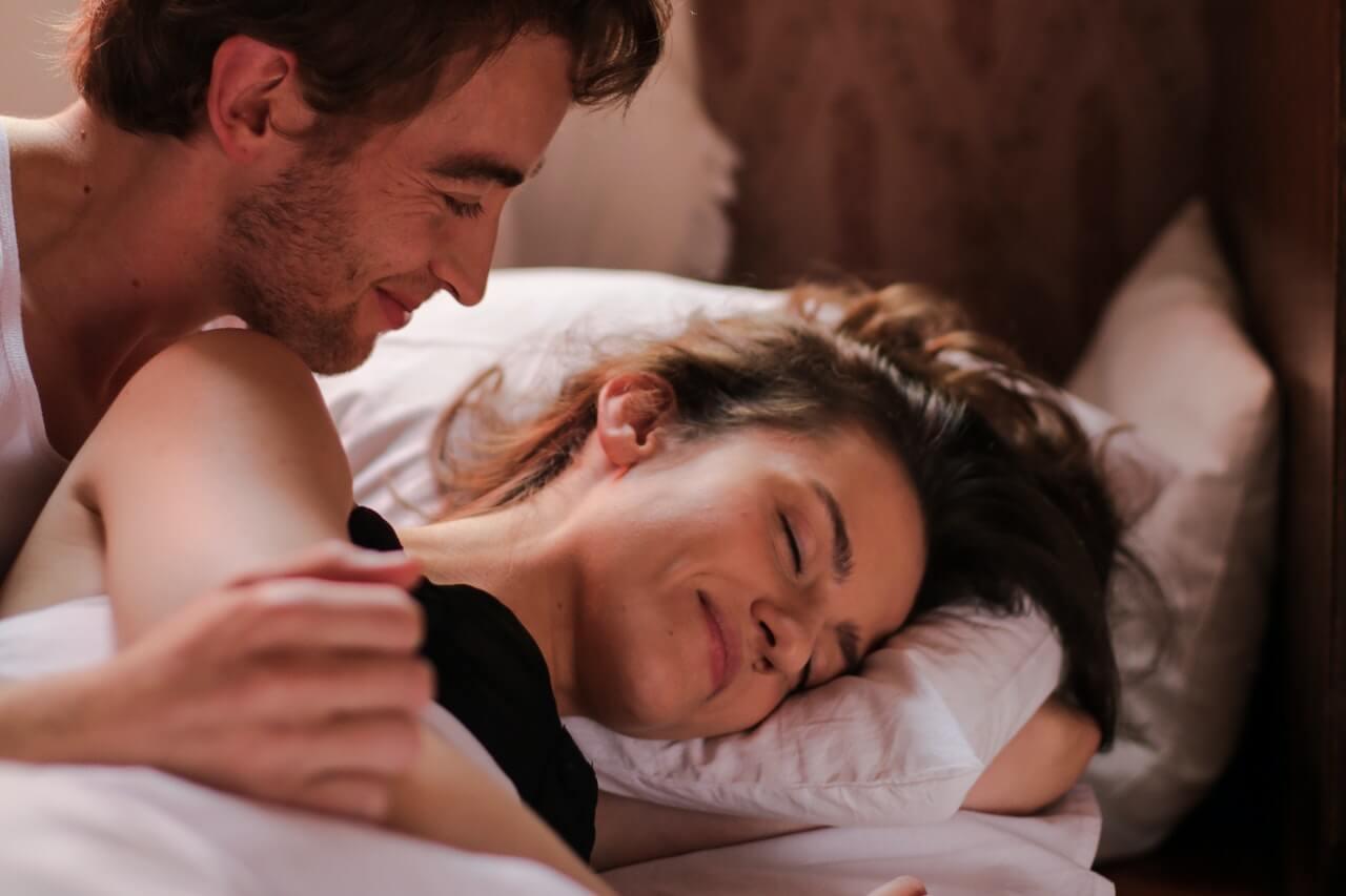 Pareja en la cama teniendo sexo sin penetración.
