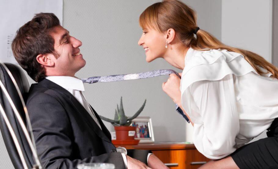 Mujer acercando a un hombre hacia ella tirándole de la corbata