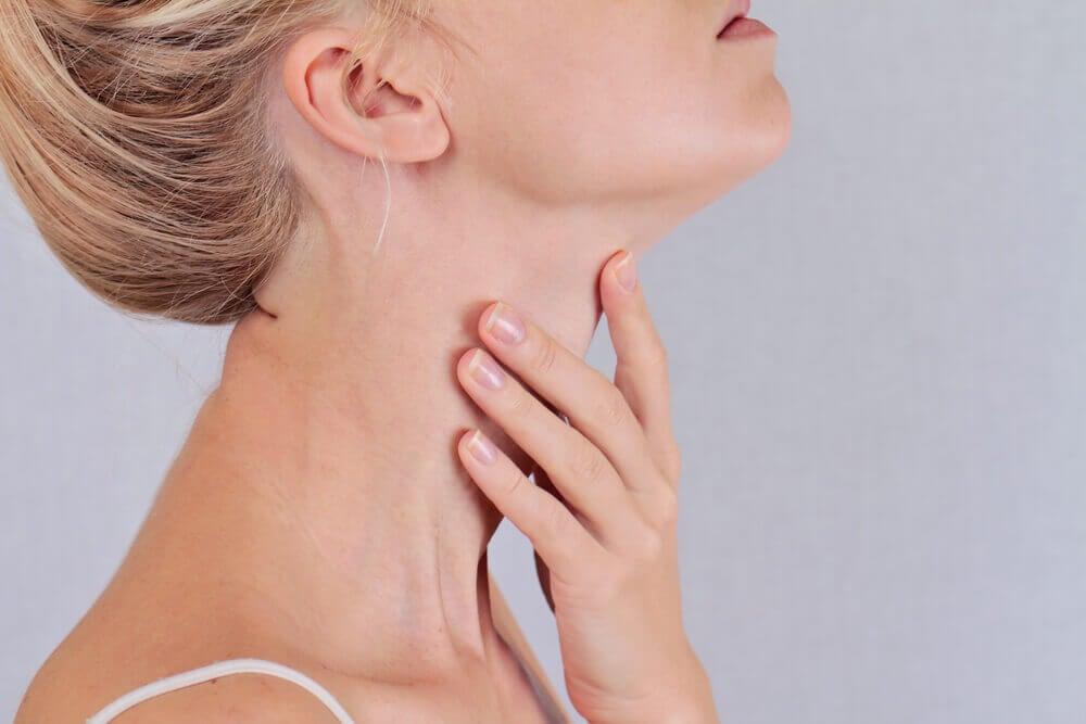 Chica tocándose la garganta en la altura de la tiroides.