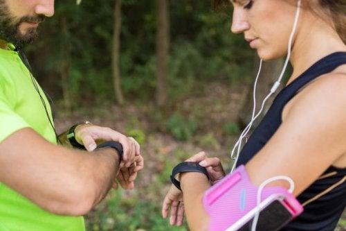 Entrenador con una chica mirando sus relojes: diferencias entre coach y psicólogo deportivo