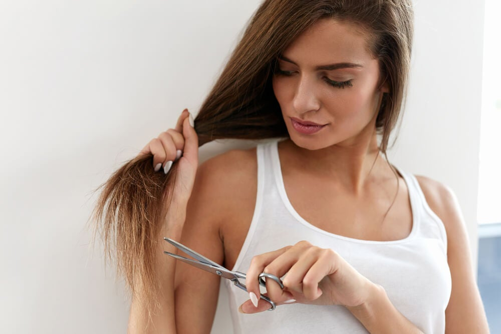 Mujer con una tijera y pelo con puntas abiertas.