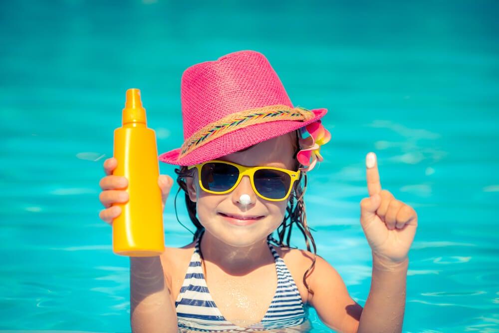 Niña con protector solar en piscina.
