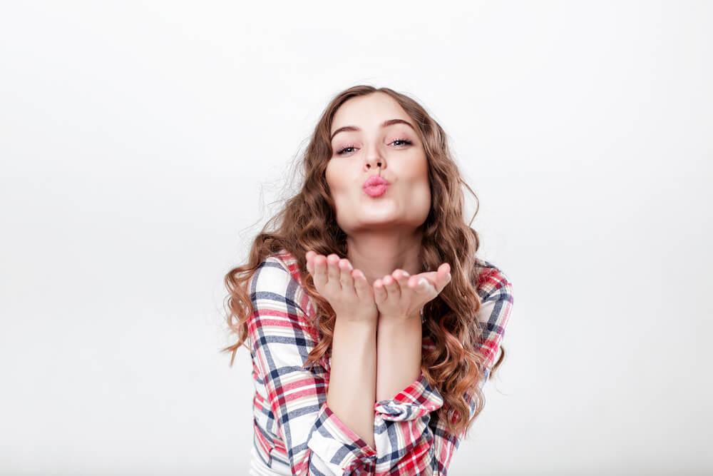Mujer joven dando un beso al aire como ejercicios para la papada.