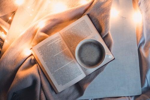 Libro con taza de té en la cama