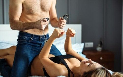Pareja practicando juegos preliminares con esposas para activar la libido