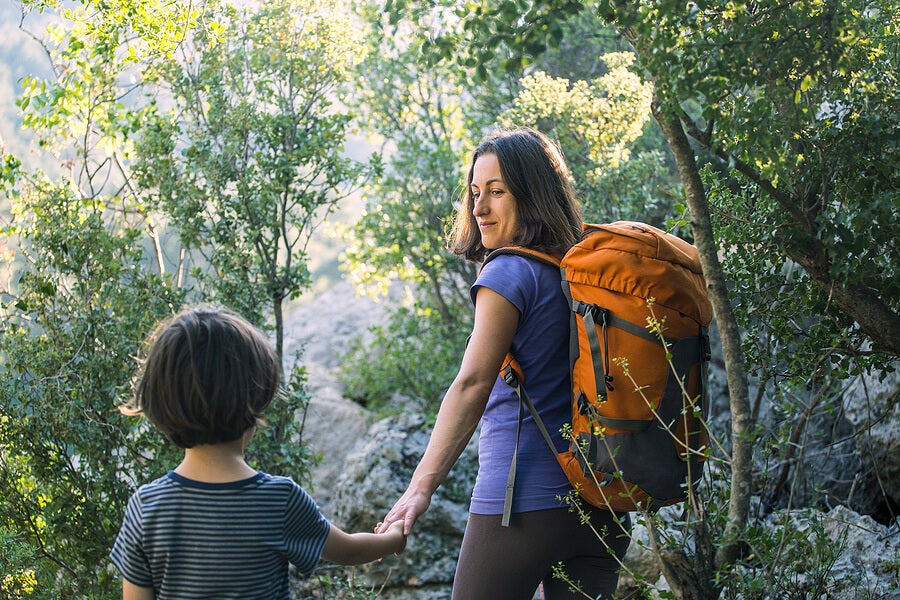 Madre e hijo cogidos de la mano por el bosque.
