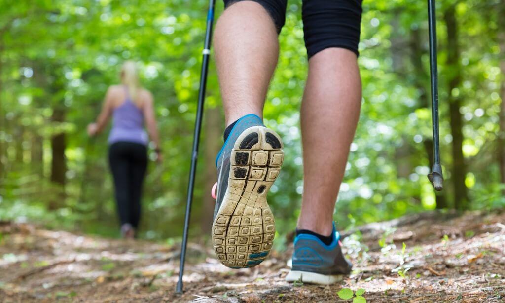 Pies con deportivas y bastones junto con una mujer en el fondo practicando la marcha nórdica.