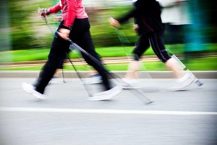 Dos personas en movimiento practican la marcha nórdica por asfalto.