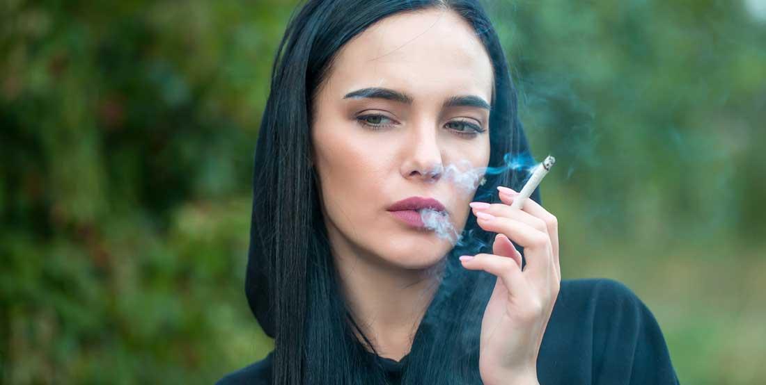 Mujer fumando un cigarro.