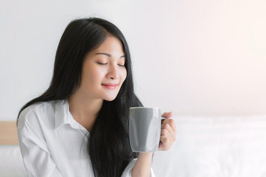 Mujer con los ojos cerrados con taza de té en la cama.