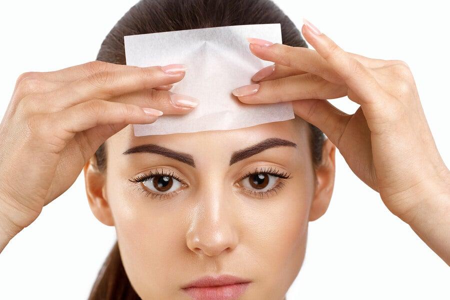 Mujer aplicándose un papel absorbente en el rostro.