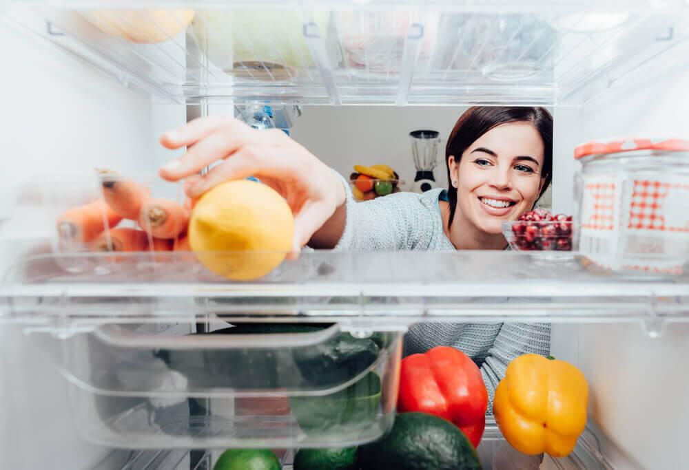 Mujer tomando un limón del refrigerador.