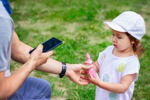 Niña perdida con adulto marcando un teléfono para localizar a los cuidadores