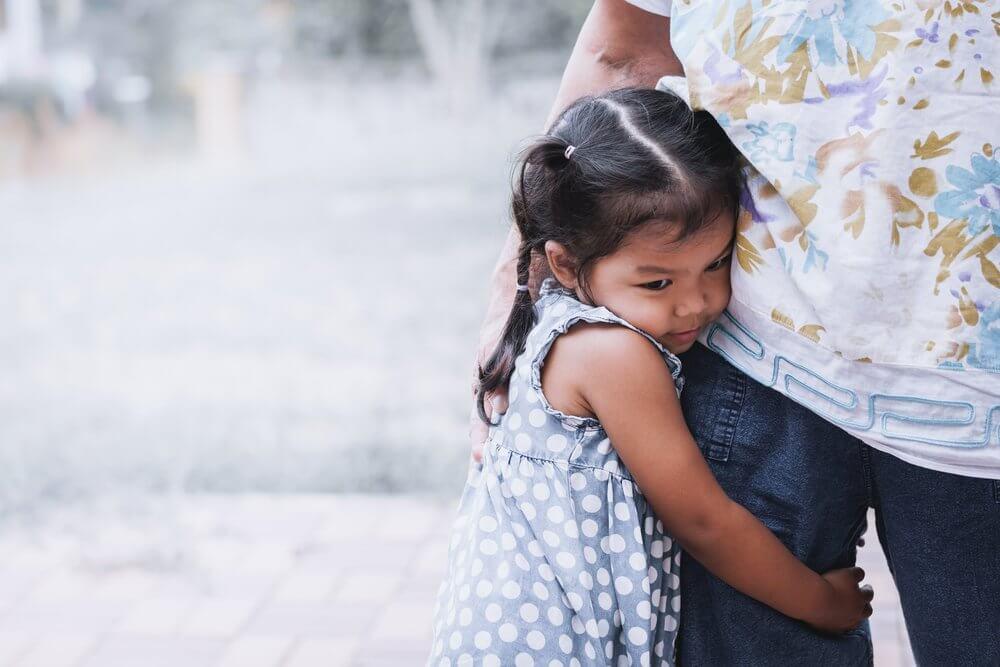 Niña agarrada a su madre antes de ir al colegio alargando la despedida, uno de los errores que comenten los padres cuando sus hijos van al colegio.