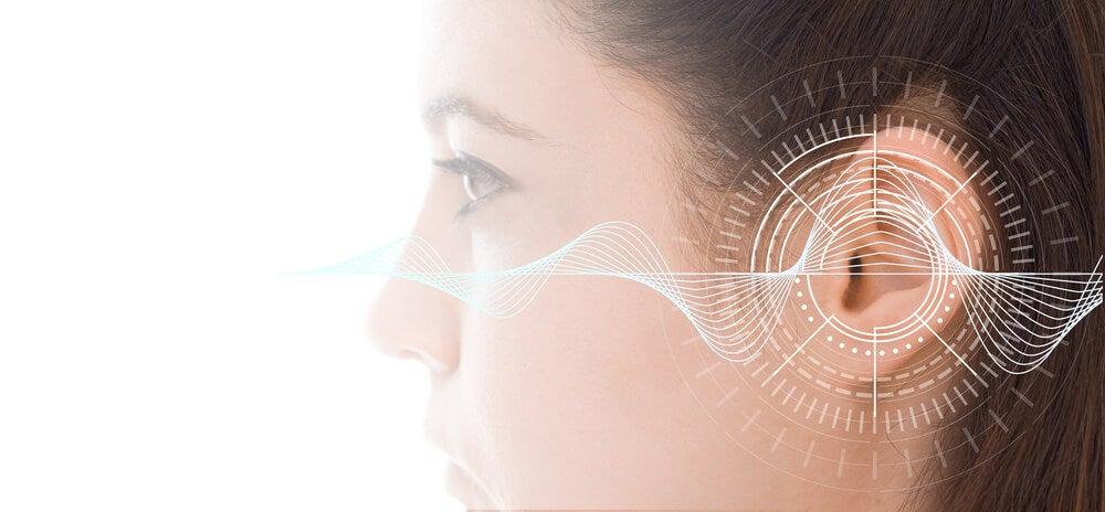 Mujer con representación de frecuencias de sonido en el oído.