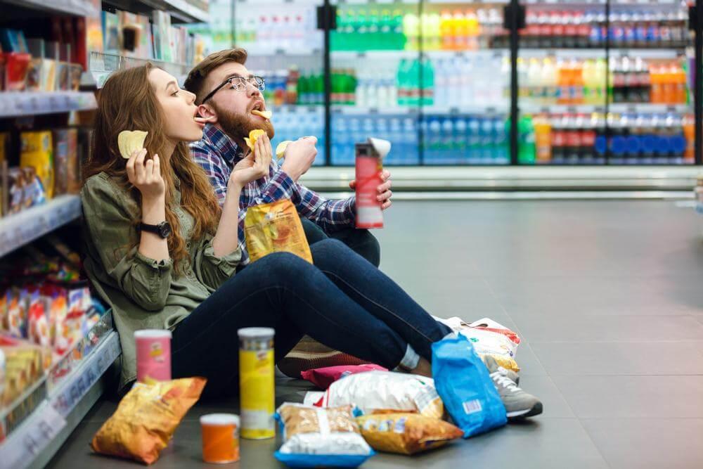 Pareja sentada en el suelo de un supermercado comiendo todo tipo de snacks.