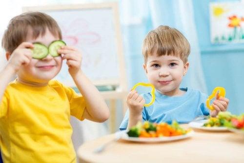 Niños pequeños jugando con verduras