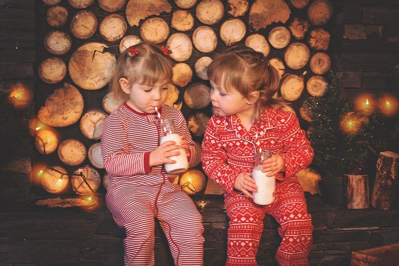 Dos niñas en pijama bebiendo leche durante una de las actividades para hacer en casa.