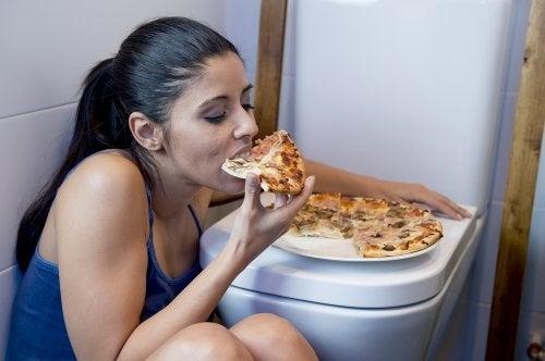 mujer comiendo pizza con ansiedad por comer