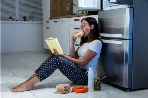 Mujer comiendo en el suelo de la cocina