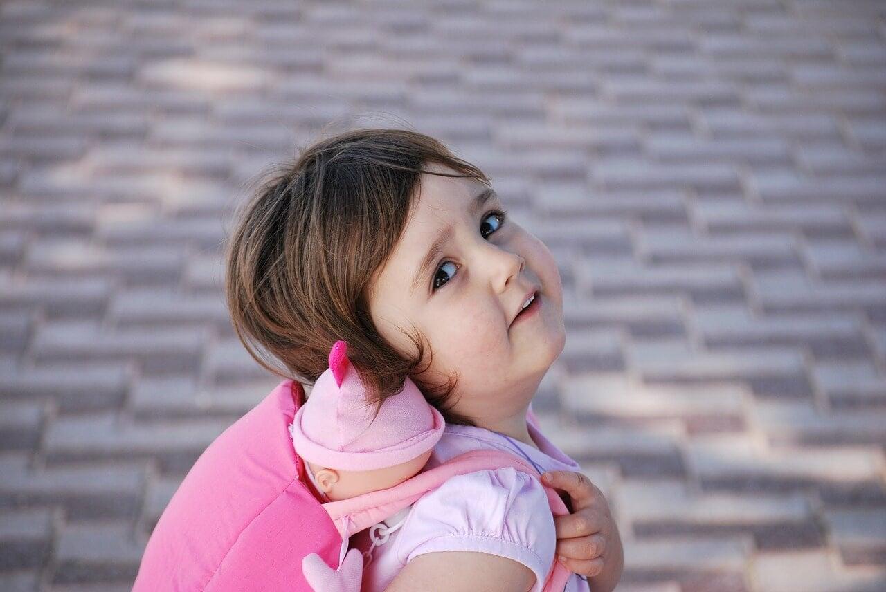Niña con mochila rosa y un muñeco dentro
