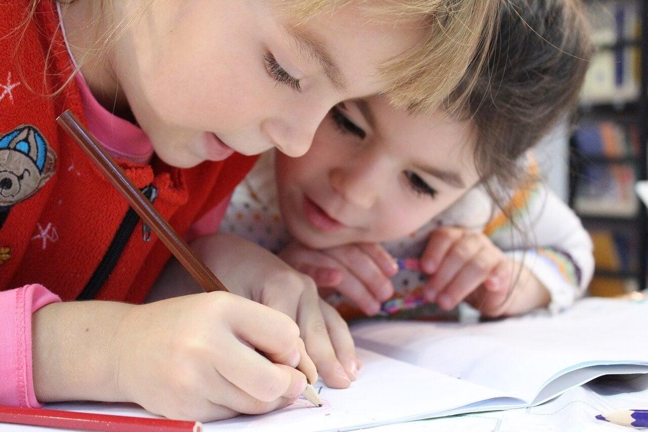 Niños dibujando con un lápiz-