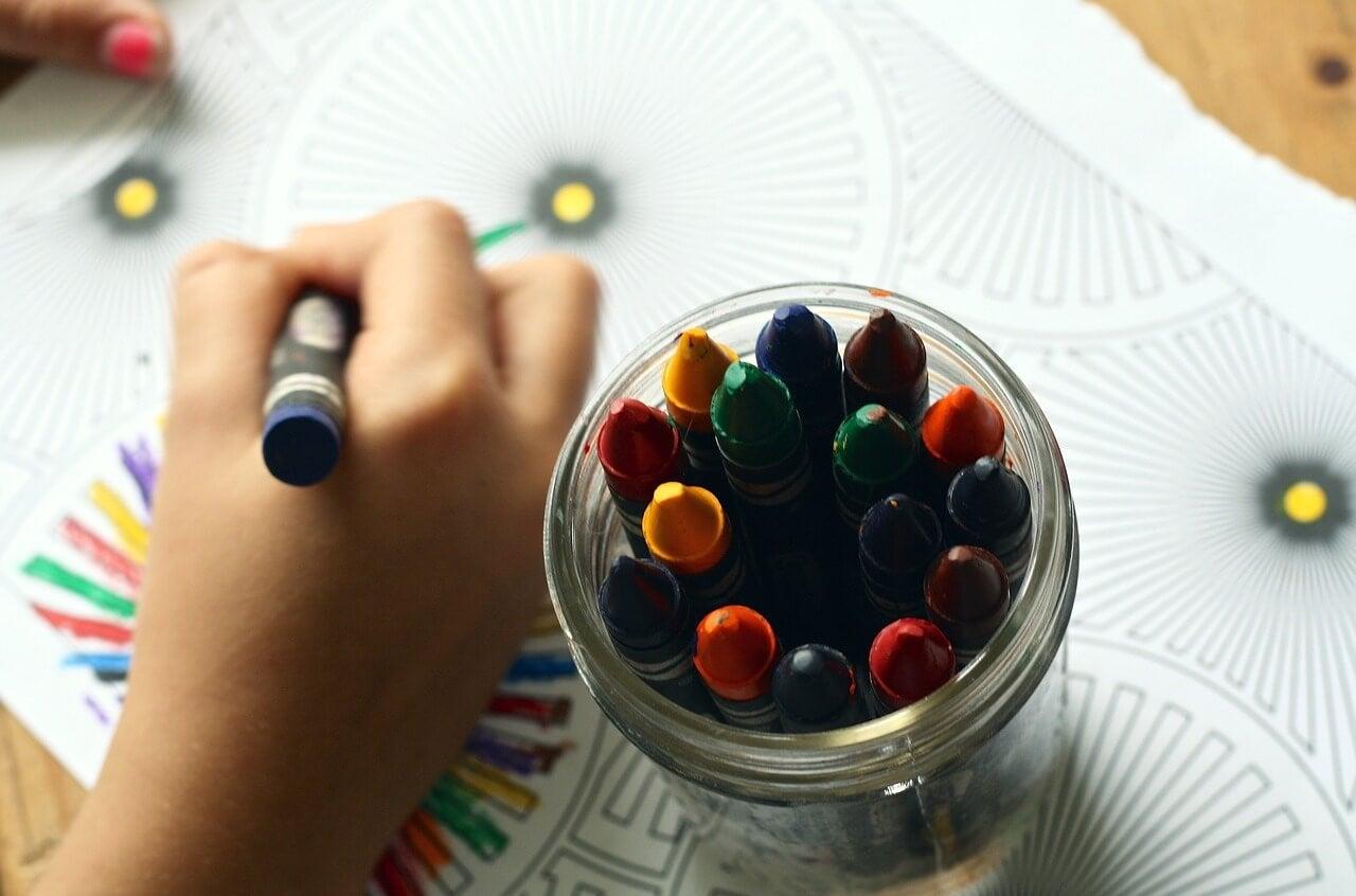 Mano de un niño dibujando y pinturas de colores.