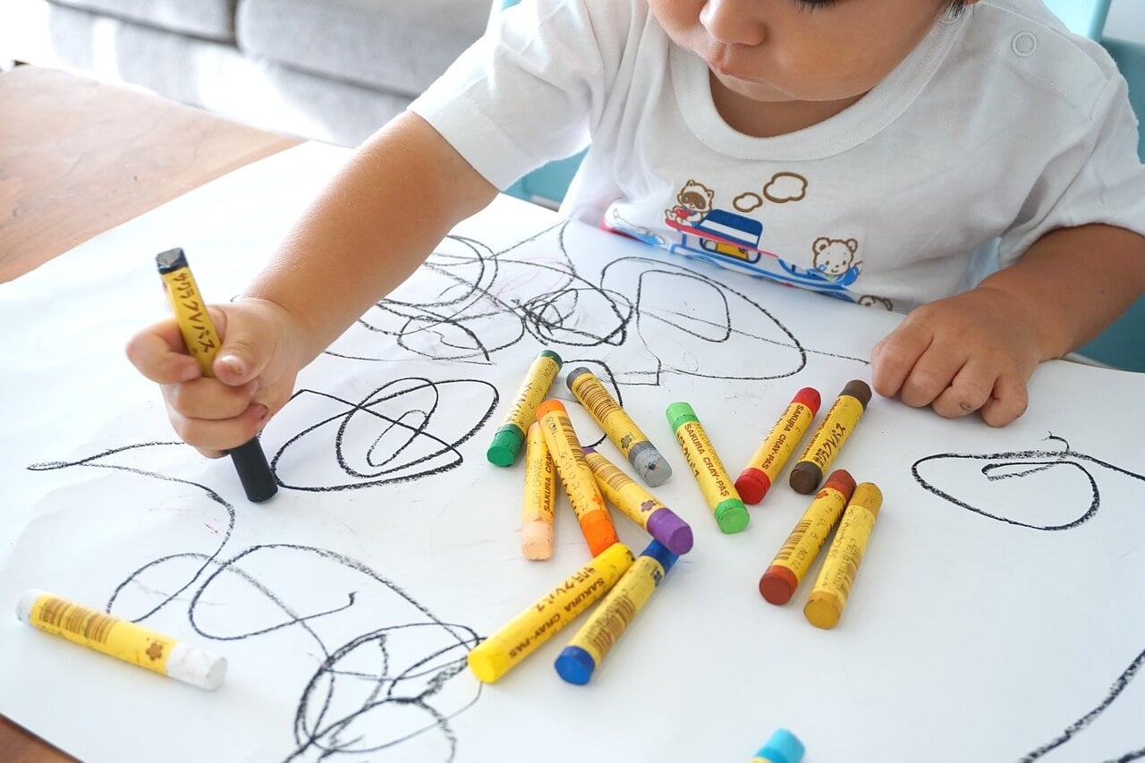 Niño dibujando con diferentes pinturas de colores.