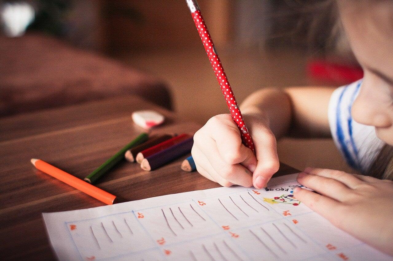 Niño dibujando con un lápiz en una hoja.