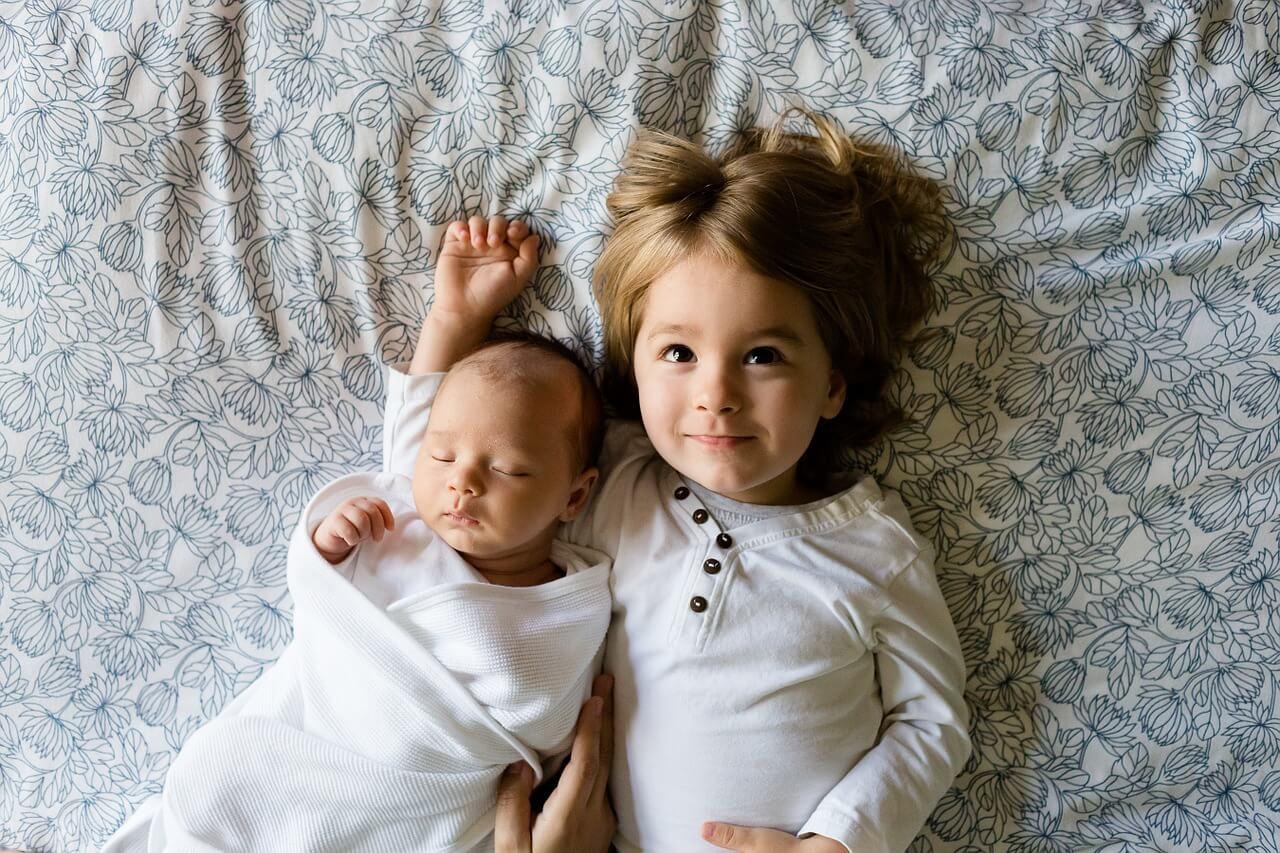 Niño y recién nacido tendidos en la cama.