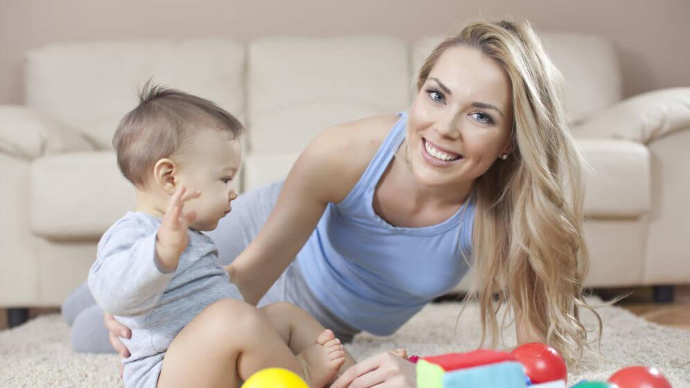 Madre e hijo jugando juntos en la alfombra.