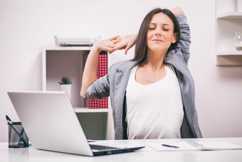 Mujer haciendo estiramientos en la oficina