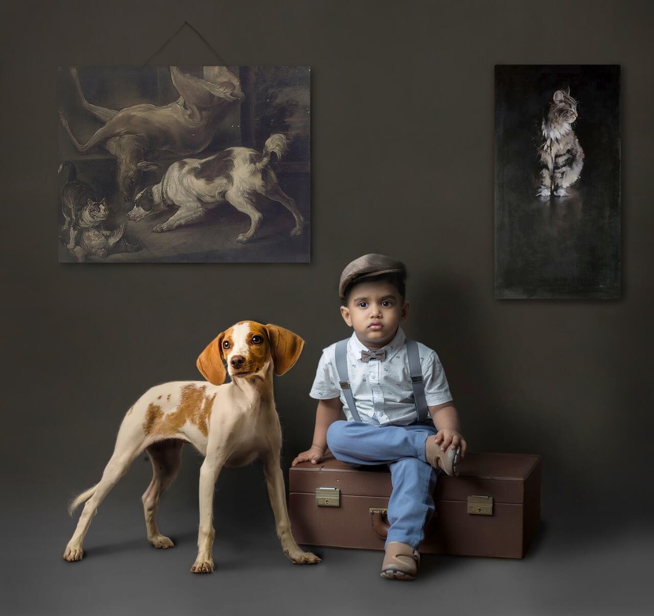 Niño sentado en una maleta acompañado de un perro con fondo oscuro y cuadros de animales.