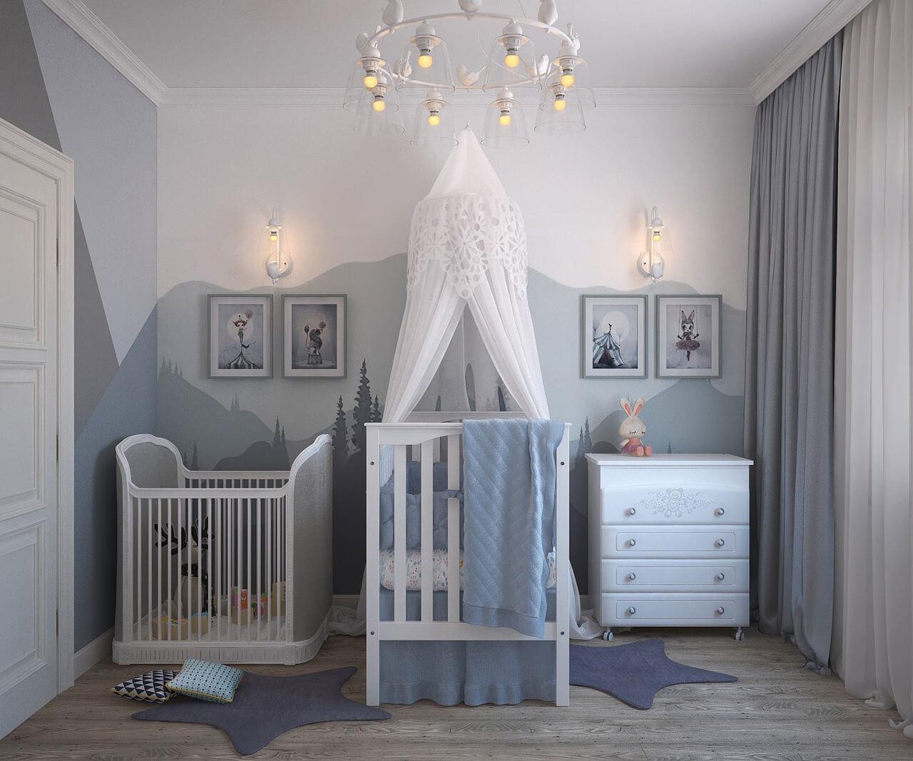 Habitación infantil con cuna y varios muebles y cuadros en tonos grises.