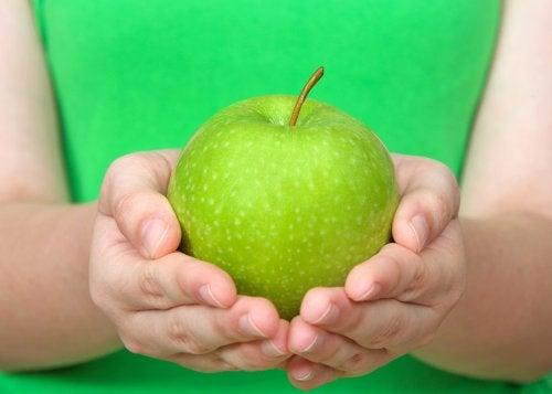 Manos de mujer sosteniendo una manzana