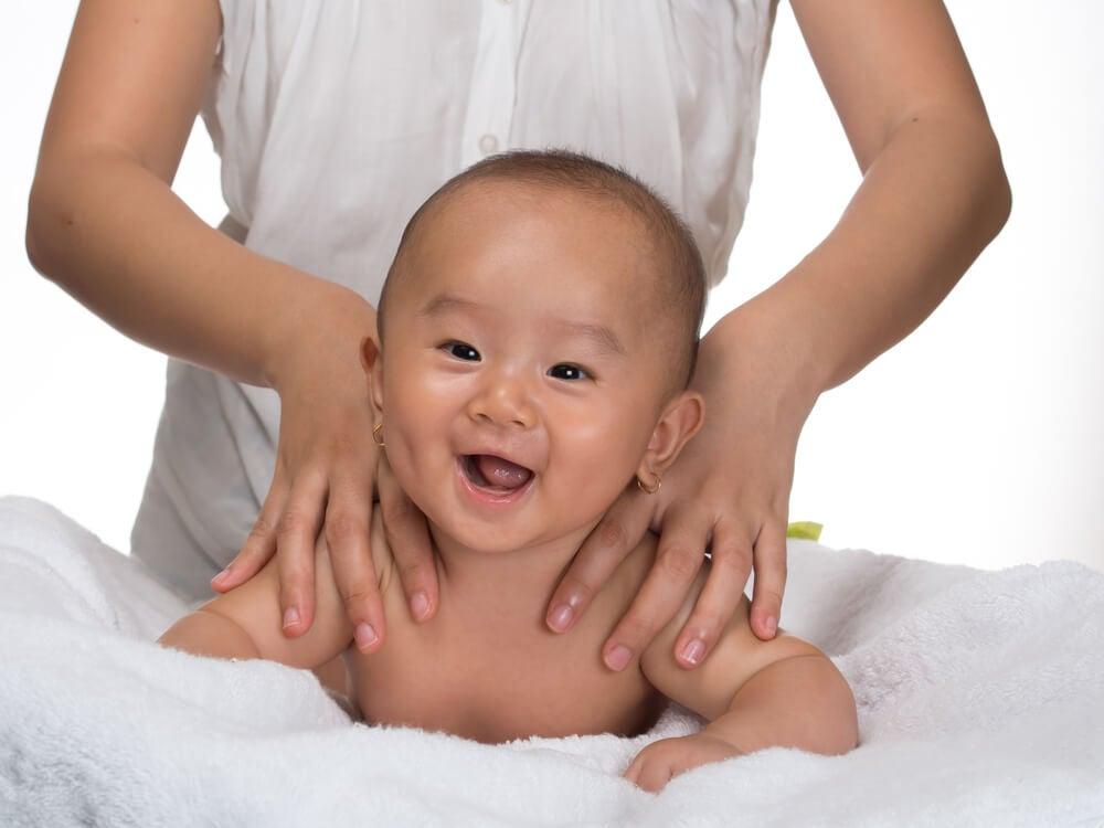 Madre dando un masaje a su hijo para activas los sentidos.