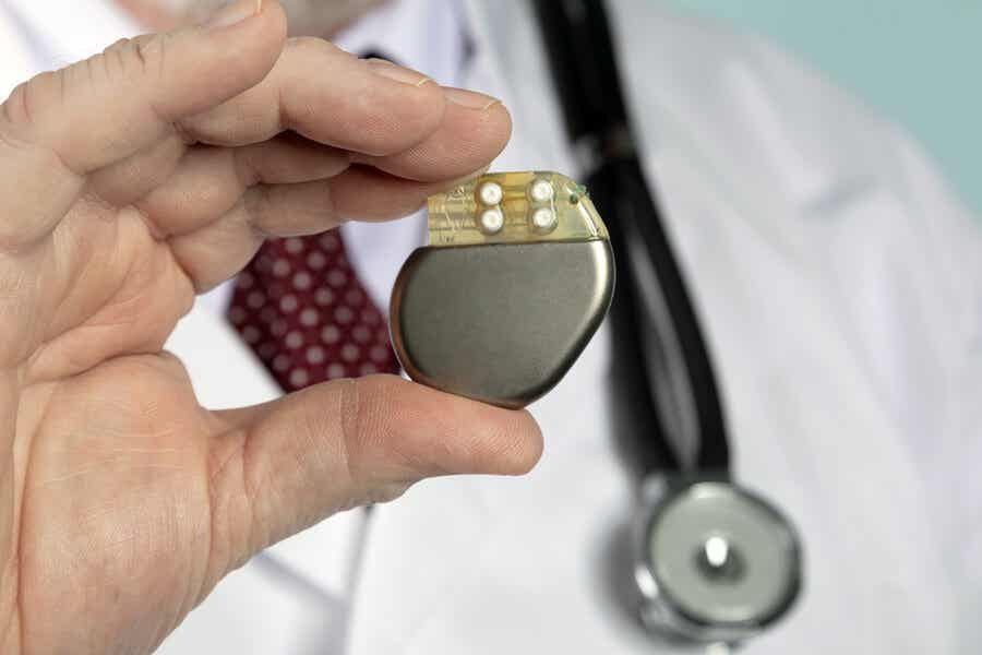 Médico sosteniendo marcapasos cardíaco.