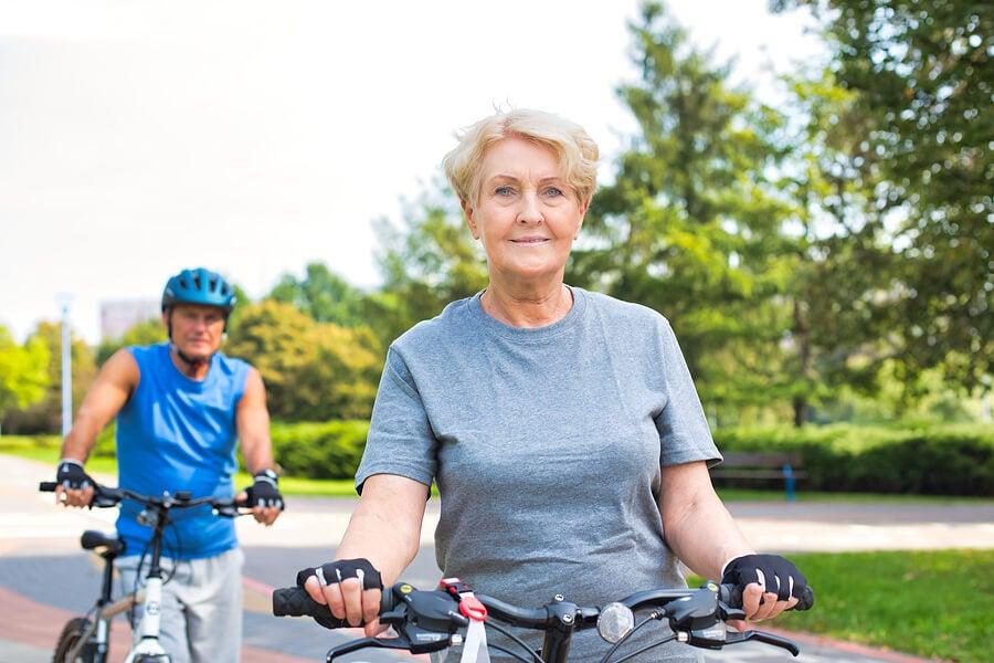 Mujer y hombre mayor paseando en bicicleta.