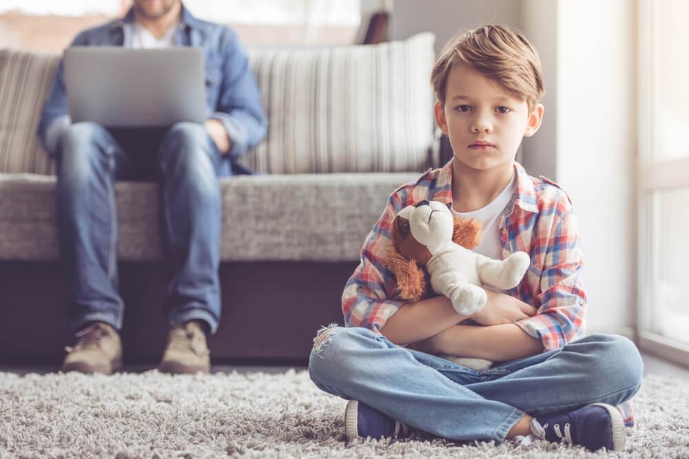 Niño sentado en la alfombra mientras su padre trabaja con el ordenador. Puede estar sufriendo maltrato.