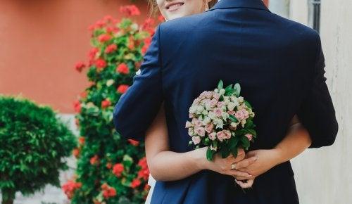 Pareja de novios recién casados abrazándose con un ramo de flores en la mano.