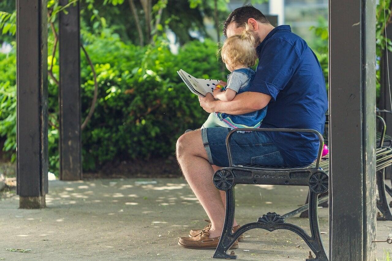 Padre enseñando a leer a un niño en el parque.