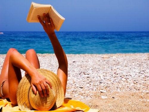Mujer tumbada en la playa leyendo un libro