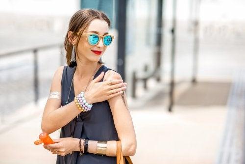 Mujer caminando por la ciudad echándose protector solar