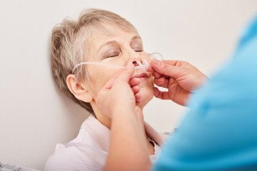Enfermero aplicando un sondaje nasogástrico a una señora mayor.