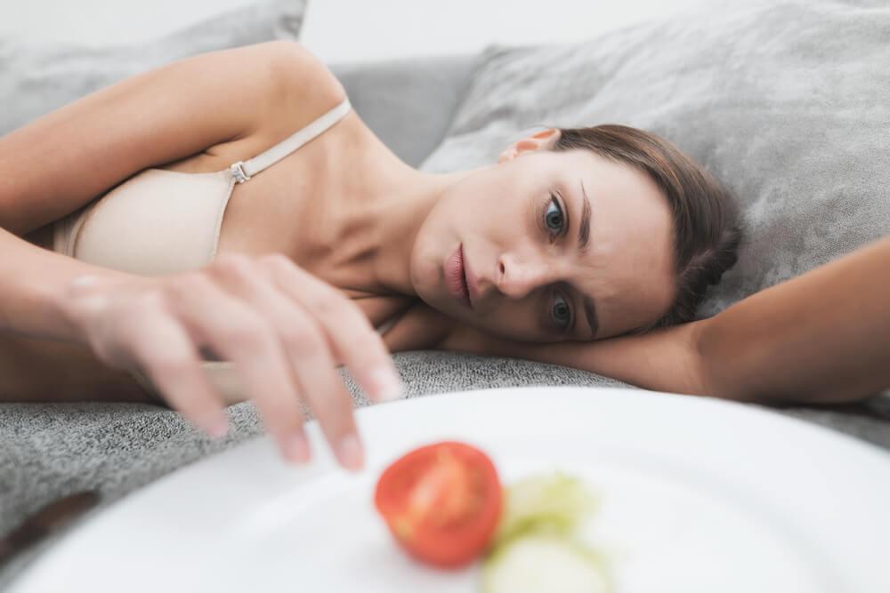 Mujer con anorexia junto a un plato de comida casi vacío.