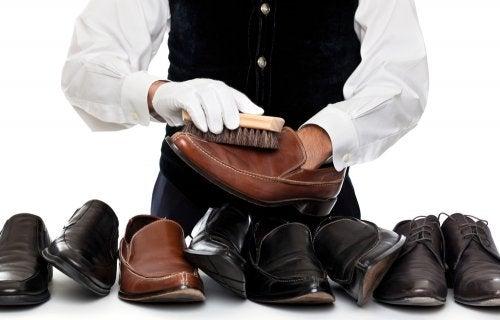 Persona limpiando un conjunto de zapatos de piel