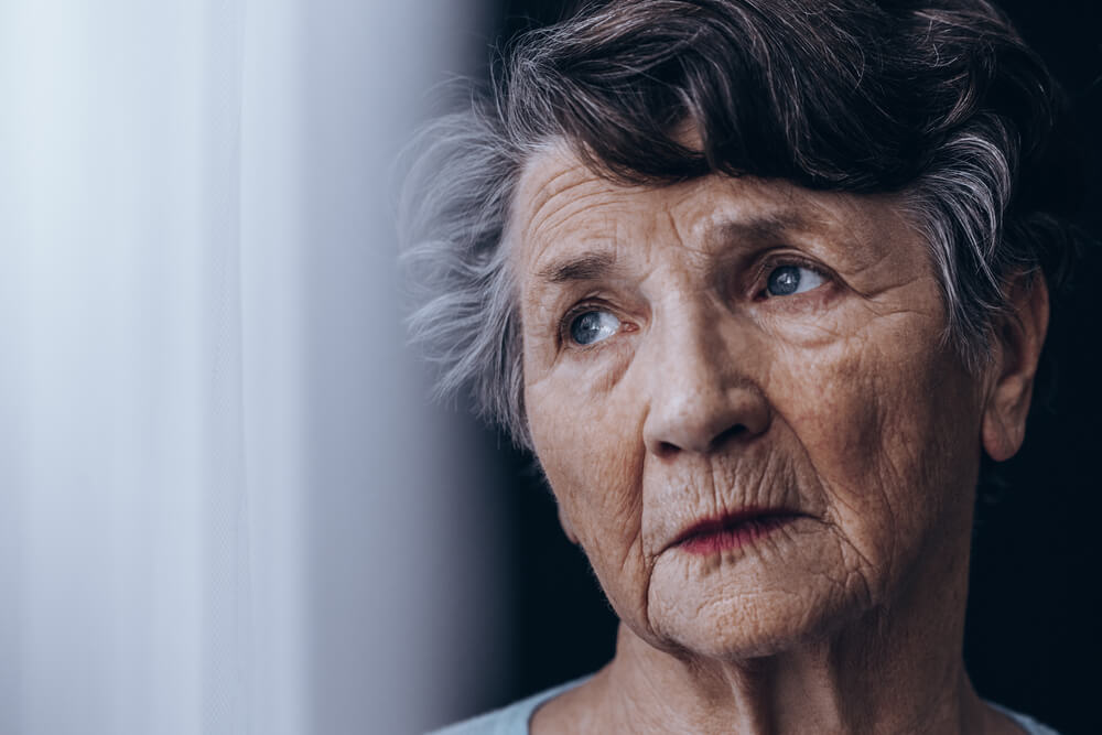 Retrato de una anciana mirando por la ventana.