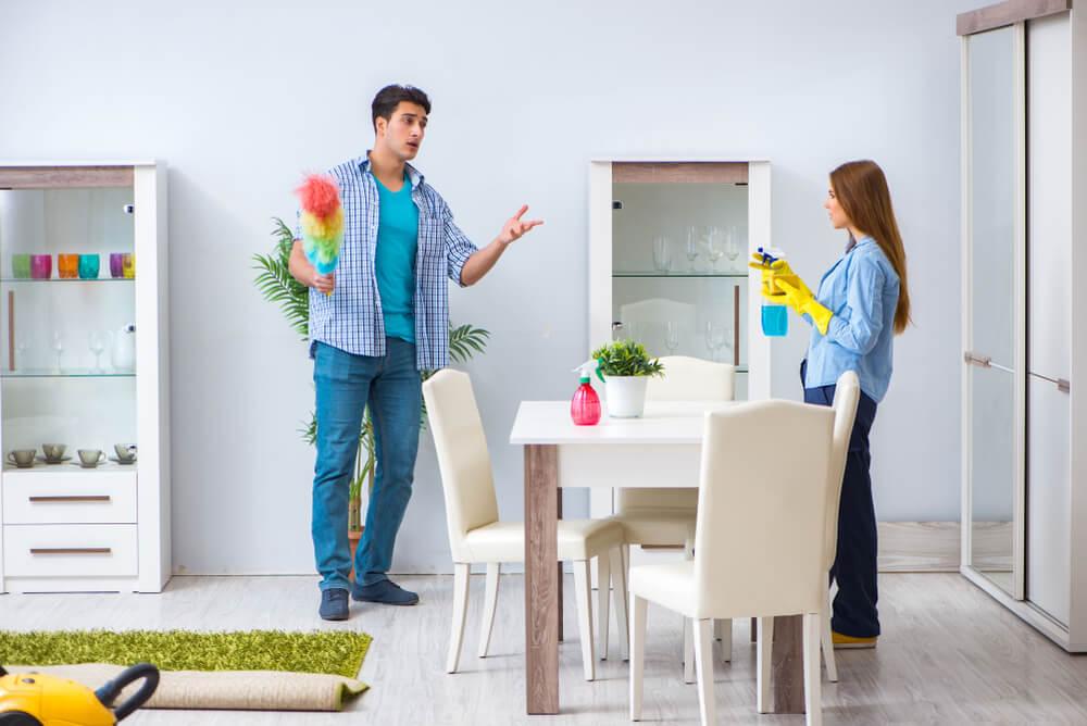 pareja discutiendo mientras limpian la casa