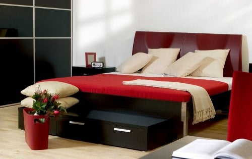 Cama con detalles rojos en una habitación moderna.